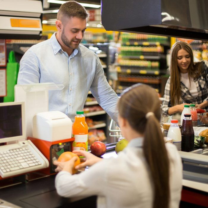 Portrait of smiling young man buying food in supermarket watching cashier scanning prices at cash desk and paying for groceries