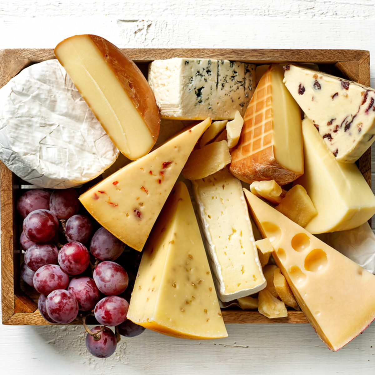 various types of cheese in wooden box on white wooden table