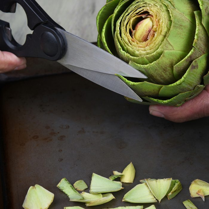 Closeup of a cook using kitchen shears to prepare an artichoke for cooking.