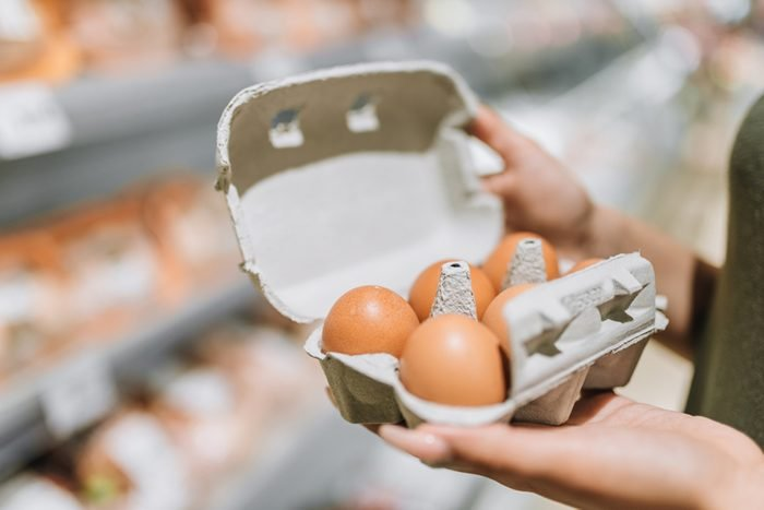 Young woman in store holding cardboard of six organic eggs.