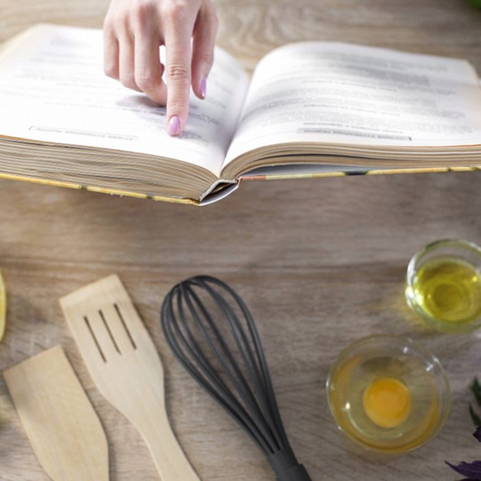 Lady reading pizza recipe in culinary book at home with kitchenware on table