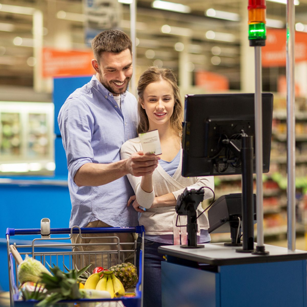 happy couple buying food at grocery store or supermarket self-service cash register