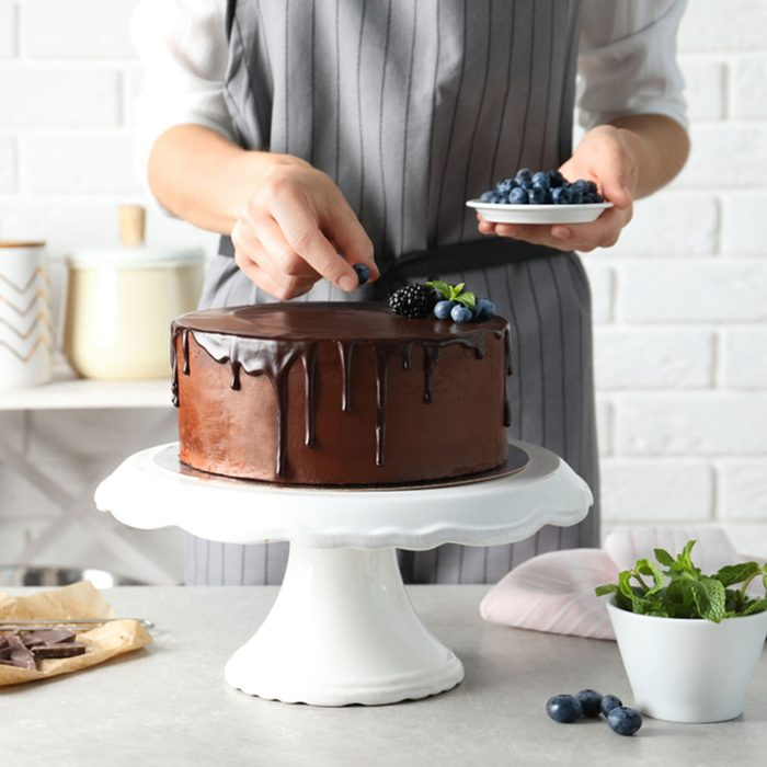 Baker decorating fresh delicious homemade chocolate cake with berries on table, closeup; Shutterstock ID 1167742222; Job (TFH, TOH, RD, BNB, CWM, CM): Taste of Home