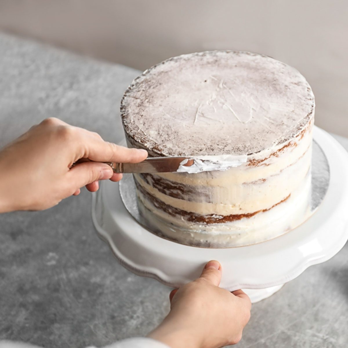 Woman decorating delicious cake with fresh cream on stand. Homemade pastry; Shutterstock ID 1174965469; Job (TFH, TOH, RD, BNB, CWM, CM): Taste of Home