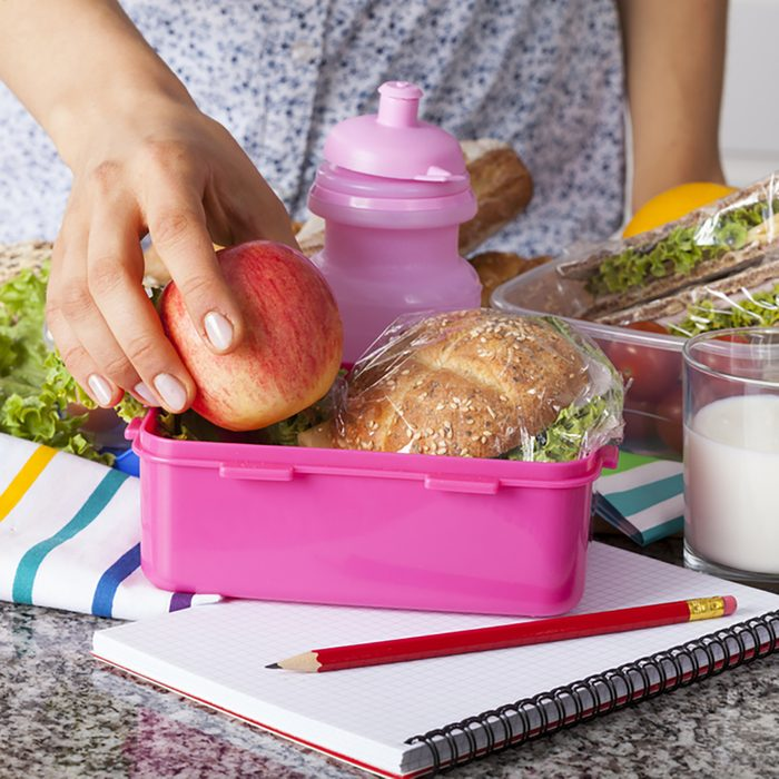Woman preparing lunchboxes with fruits and sandwiches for school