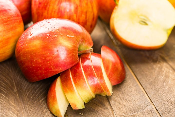 Variety of organic apples sliced on wood table.; Shutterstock ID 322257455;