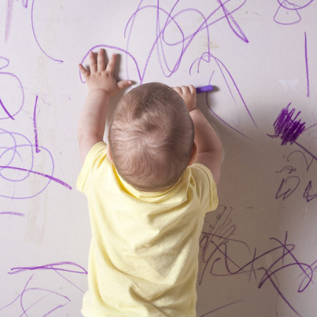 Baby boy drawing with wax crayon on plasterboard wall. He is with his back towards; Shutterstock ID 441125365