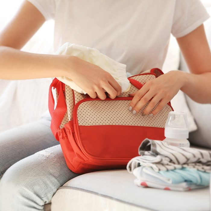 Woman packing her bag with child stuff on couch; Shutterstock ID 520971703; Job (TFH, TOH, RD, BNB, CWM, CM): Taste of Home