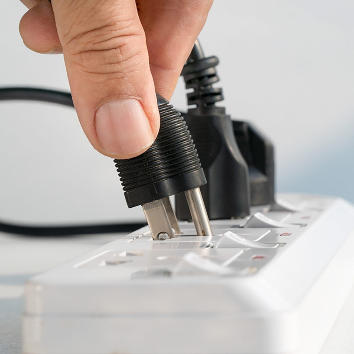 Close up Elderly hand plugging into electrical outlet;