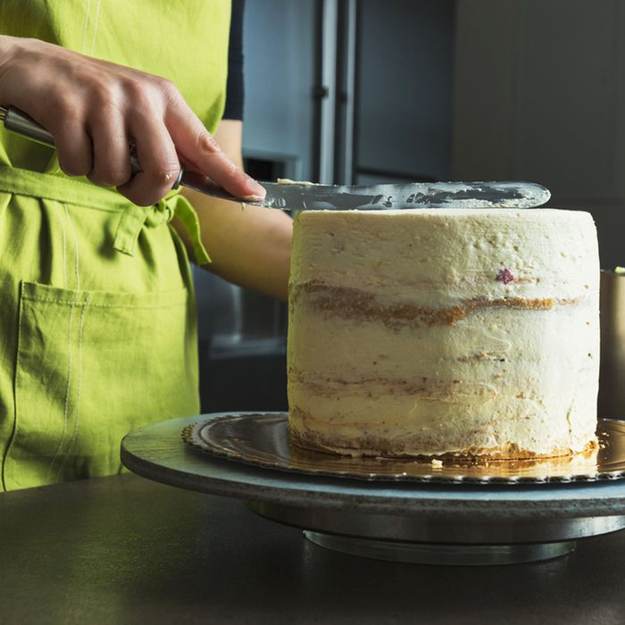 woman showing how to frost a cake