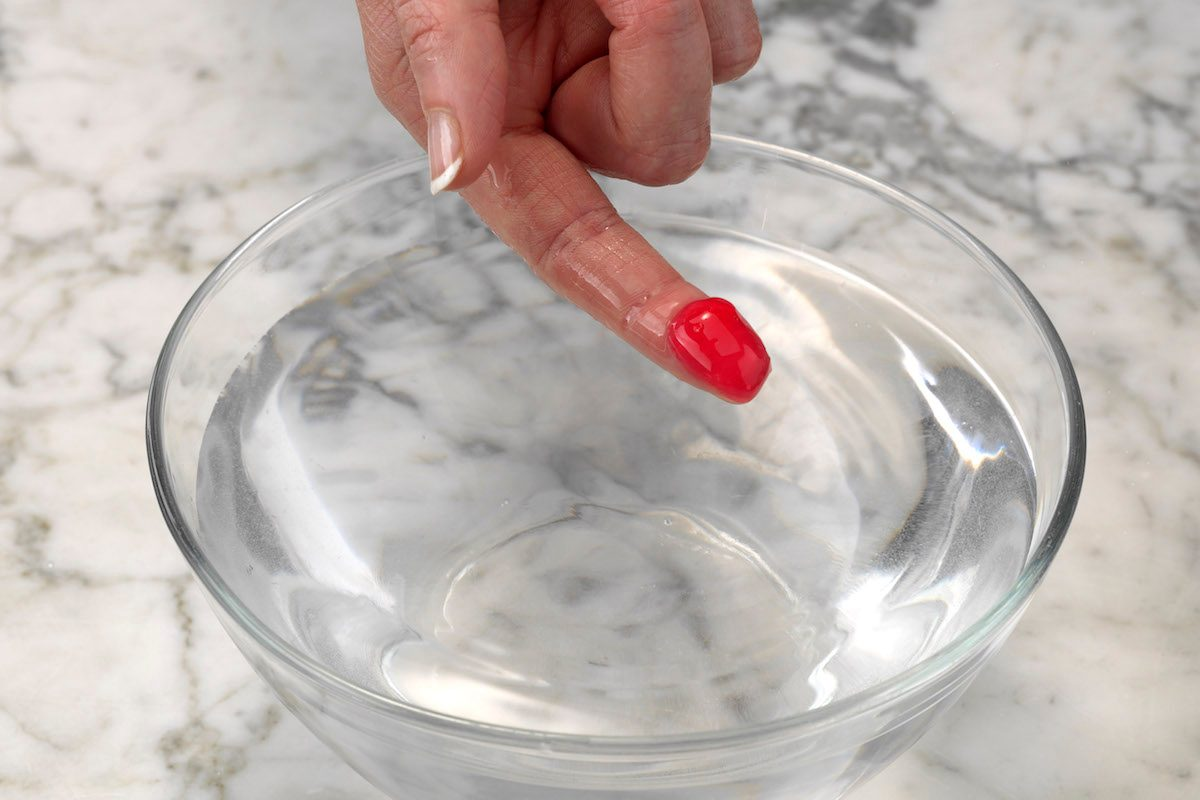 Testing red homemade candy using the cold water test. The mixture is flat after being removed from cold water, meaning it's in the soft-ball stage.