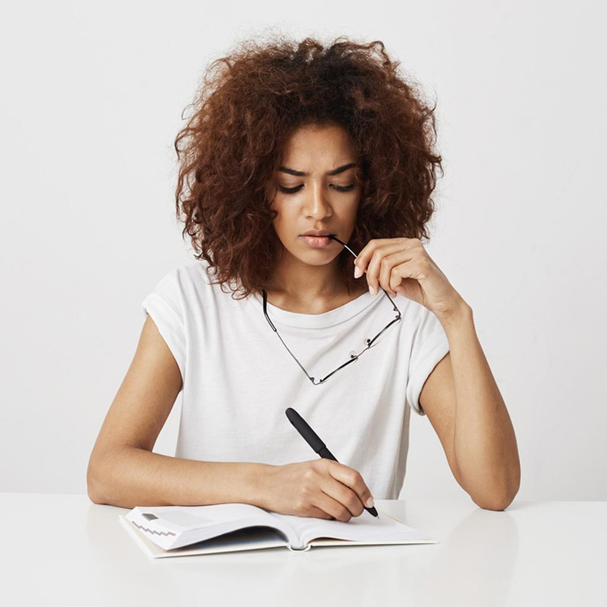 Woman thinking and taking notes