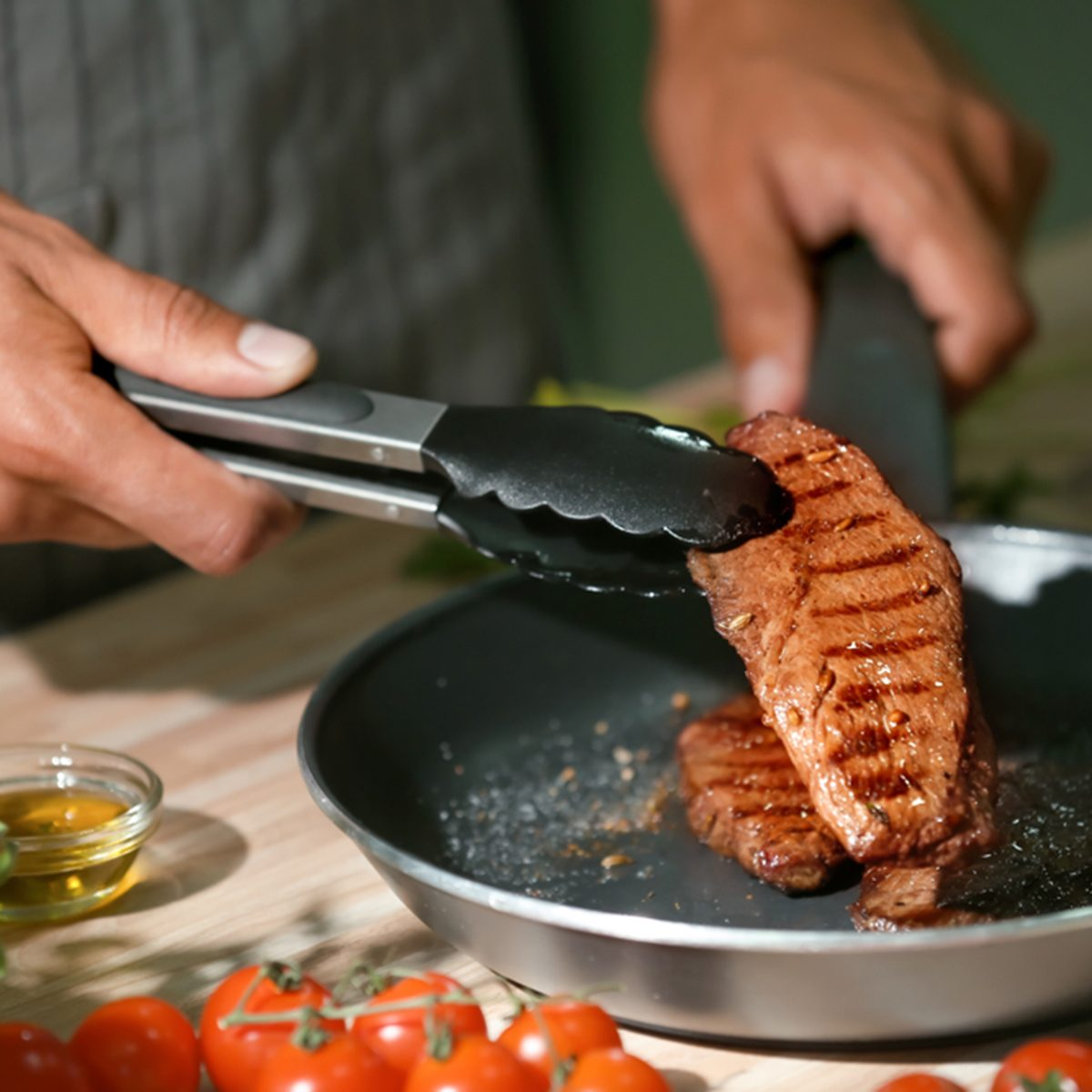 Man holding delicious roasted meat with tongs in kitchen