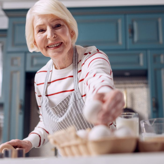 The focus being on a pleasant elderly lady taking an egg from an egg carton and smiling at the camera while making dough for a pie