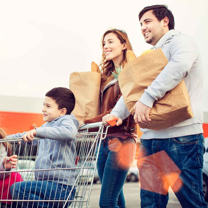 Family carrying groceries to car