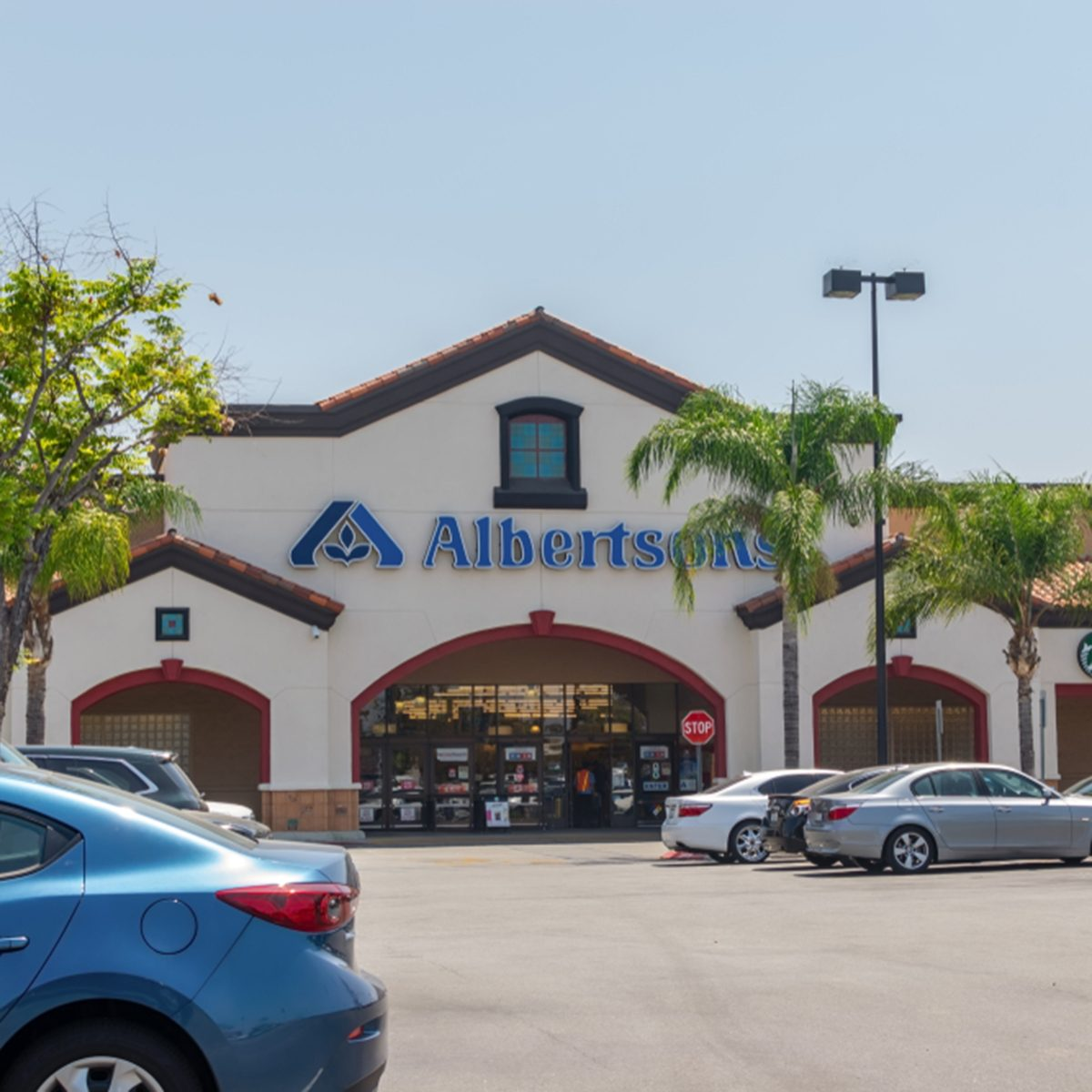 Albertsons grocery store entrance with a Starbucks and Savon Pharmacy inside the store.