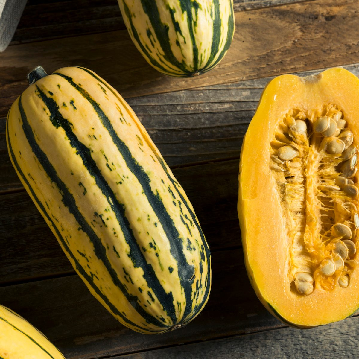 Two deliata squash—one whole and one sliced in half vertically.