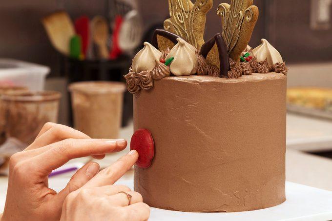 Putting nose on reindeer cake