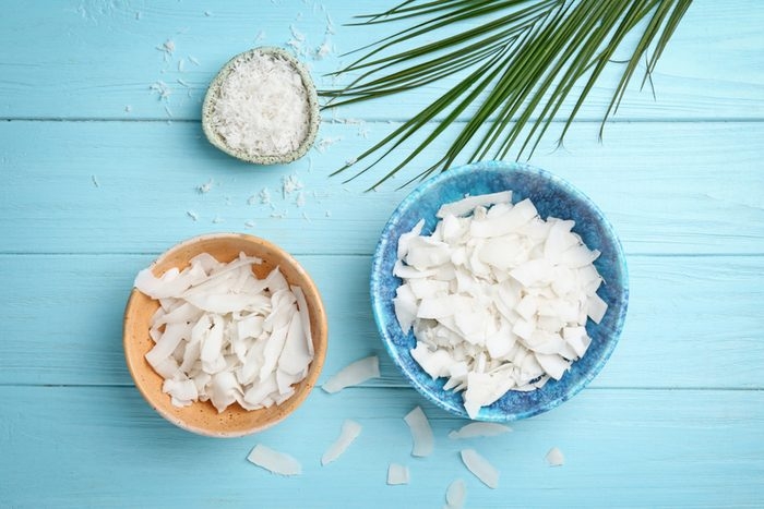 Bowls with coconut flakes on color wooden background