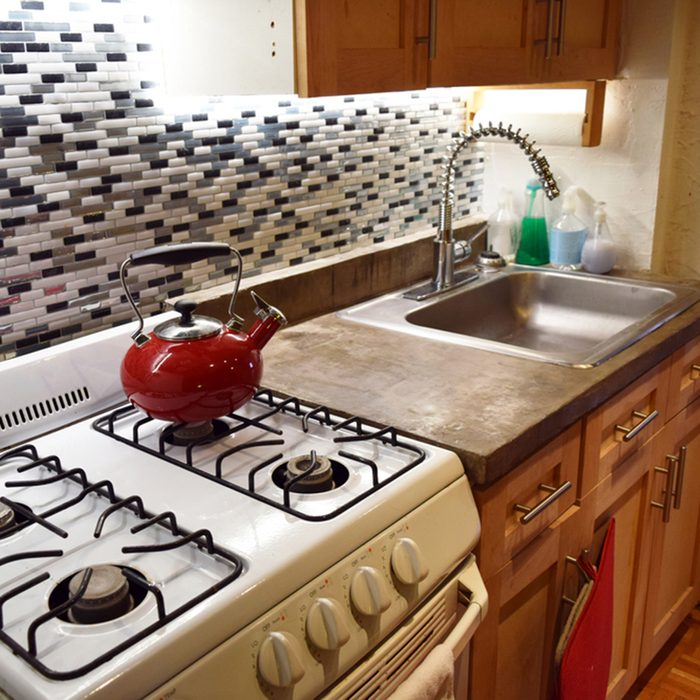 Clean kitchen with kettle on stovetop and concrete countertops in an apartment