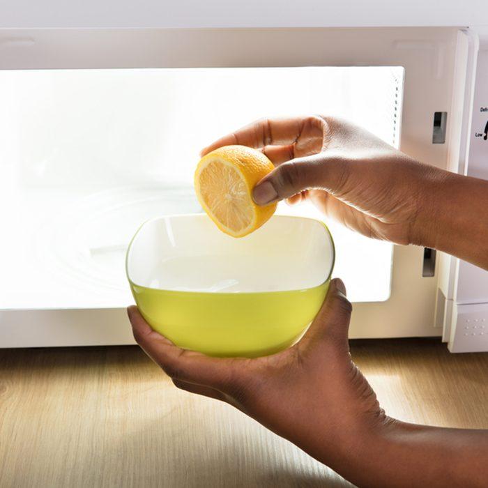 Human Hand Putting Sliced Lemon In Bowl Near Open Microwave