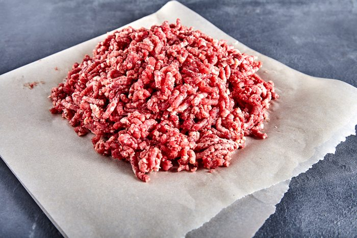 Pinky raw ground beef on a craft paper.