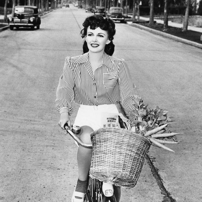 Young woman riding her bicycle with basket full of flowers and carrots; Shutterstock ID 100085855; Job (TFH, TOH, RD, BNB, CWM, CM): Taste of Home