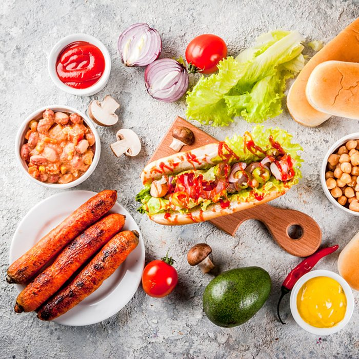 Ingredients for different homemade Vegan Carrot Hot Dogs, with fried onion, avocado, chili, mushrooms, tomatoes and beans