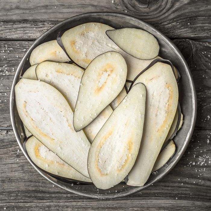 Sliced eggplants with salt in the metal plate on the wooden table top view