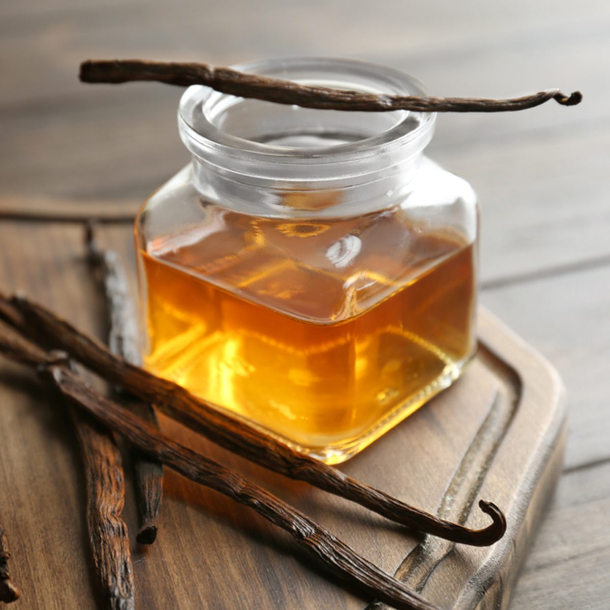 Jar with vanilla extract and sticks on wooden board