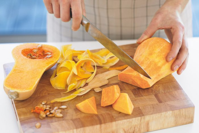 A person cutting a butternut squash on a wooden cuting board.