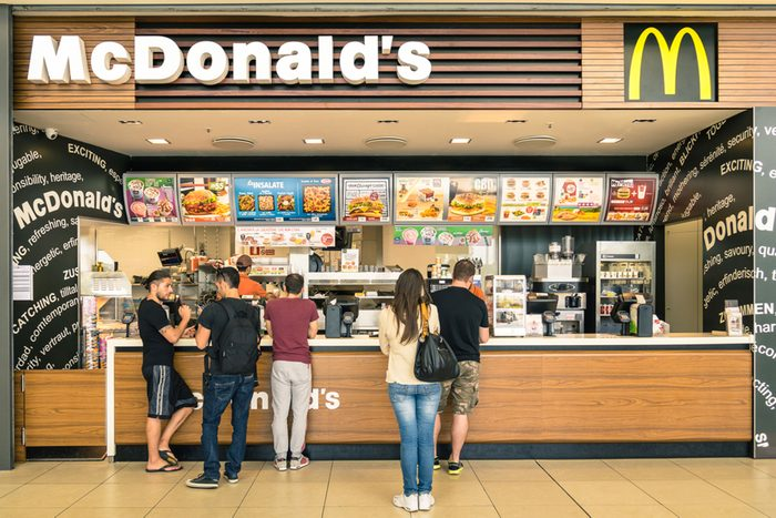 """people waiting for the food service at Mc Donalds desk in the shopping mall """"Le Befane"""""""