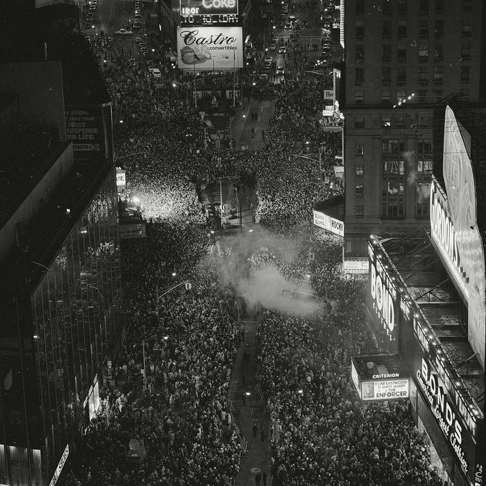 As a smoke bomb goes off at center, revelers welcome 1977 at New York's Times Square Friday night