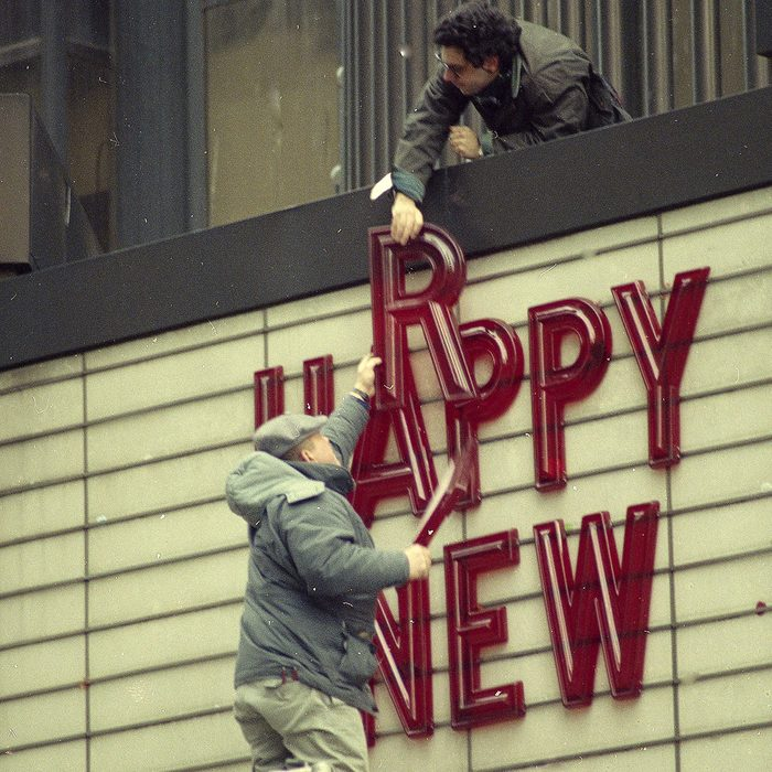 """Joe Kafka, below, hands an unidentified co-worker letters from a """"Happy New Year"""" marquee on the Cineplex Odeon movie theater in New York's Times Square, the morning after revelers rang in the new year"""