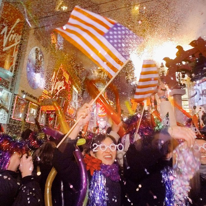 Mizumi Malfitamo from Italy waves an American flag in celebration as the new year arrives at Times Square in New York City