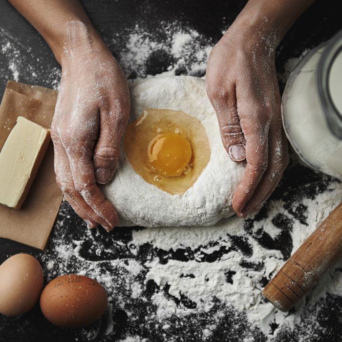 Professional female baker cooking dough with eggs, butter and milk for Christmas cookies.