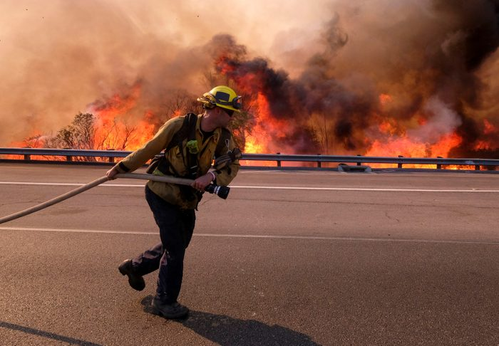 Firefighters battle a fire along the Ronald Reagan (118) Freeway in Simi Valley, Calif