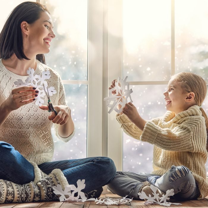 Happy loving family sitting by the window and making paper snowflakes for decoration windows.