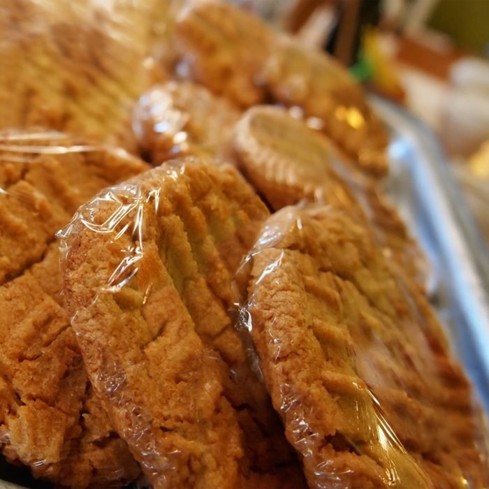 Freshly baked peanut butter cookies in plastic wrap at a coffeehouse bakery counter.