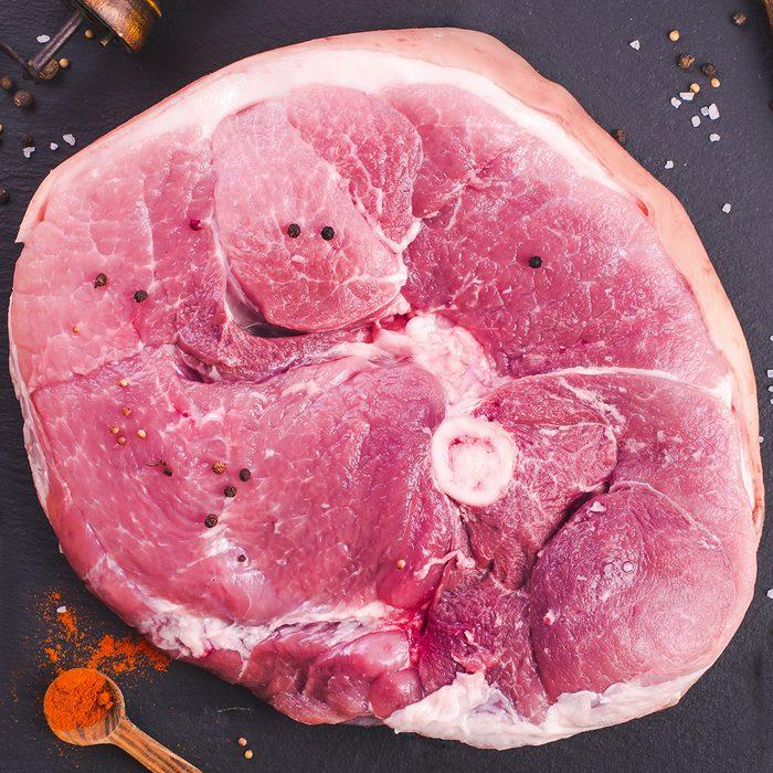 Raw ham cut and kitchen utensils top view