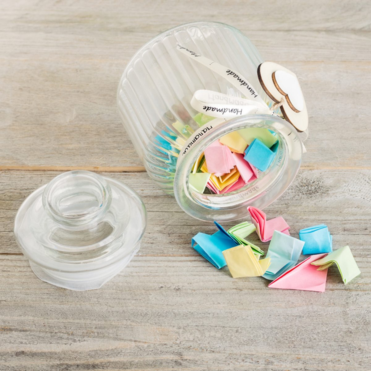 Glass jar with handmade wooden hearts decorations and ribbon filled with colorful pastel paper notes spilling over.; Shutterstock ID 696530689; Job (TFH, TOH, RD, BNB, CWM, CM): TOH