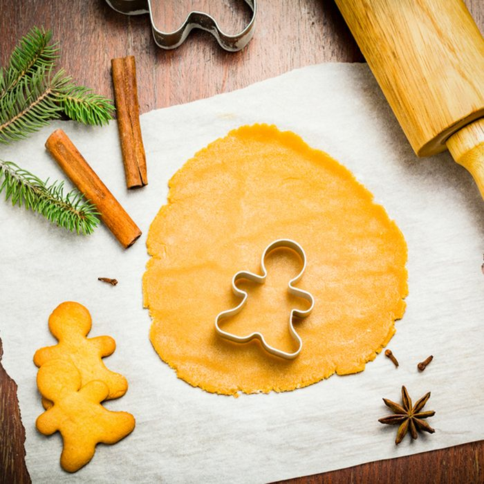 Gingerbread cookies, cookie dough and Christmas decorations on wooden table