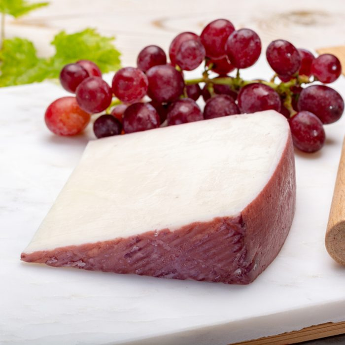 Traditional Spanish cheese, one piece of Murcian wine cheese from goat milk with rind washed in red wine, served with fresh ripe grapes