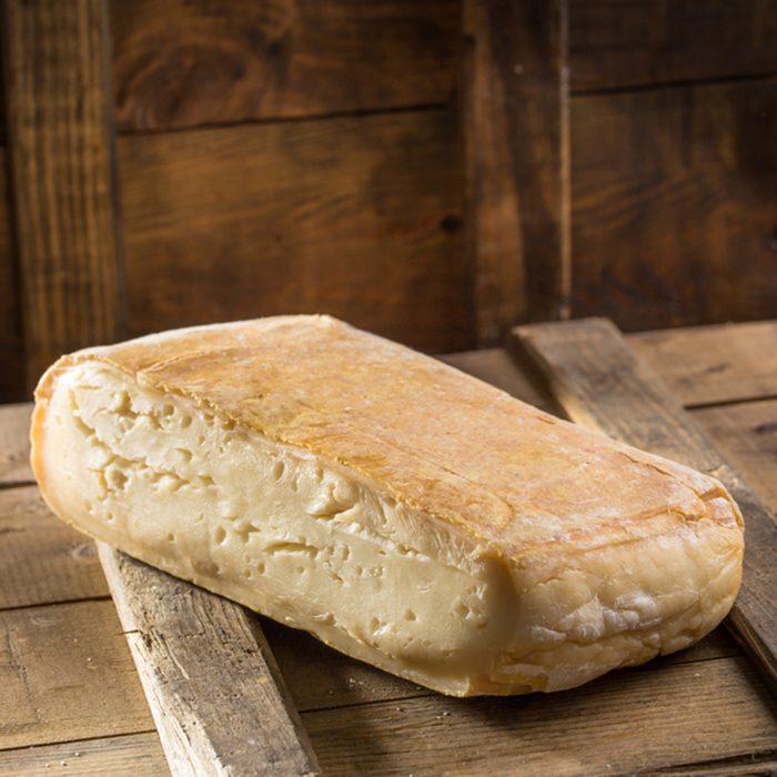 Piece of taleggio cheese on wooden board on dark background.