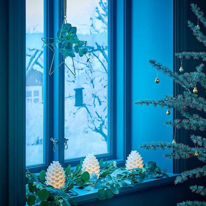 Light-up pinecones on window ledge