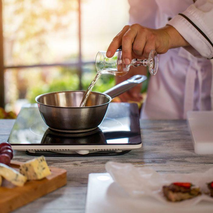 Glass pouring liquid on saucepan.