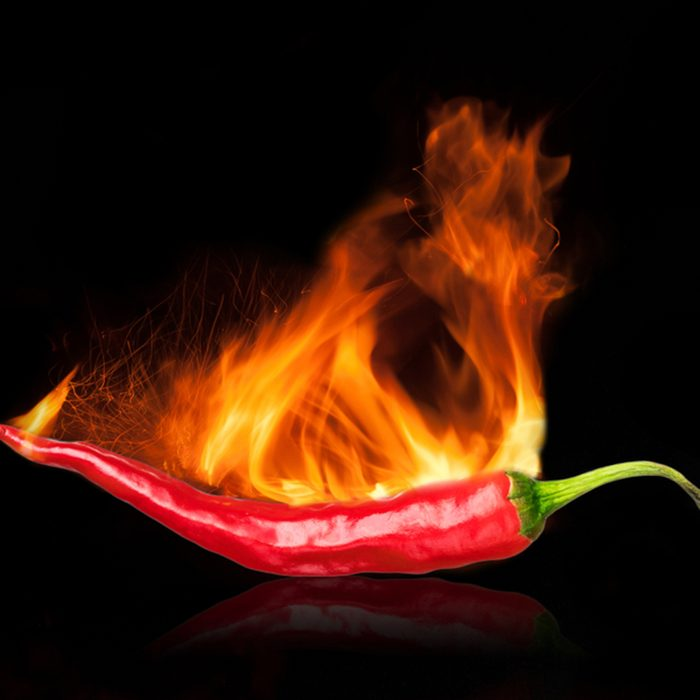 single red chili peppers with fire on black background