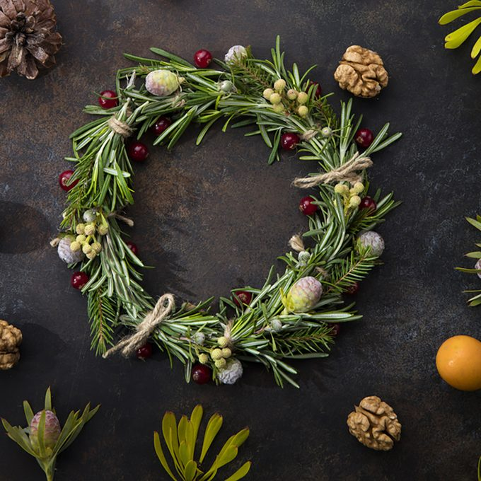 Christmas wreath of rosemary on a beautiful brown background, with berries, cones, currants, twigs and leaves around.