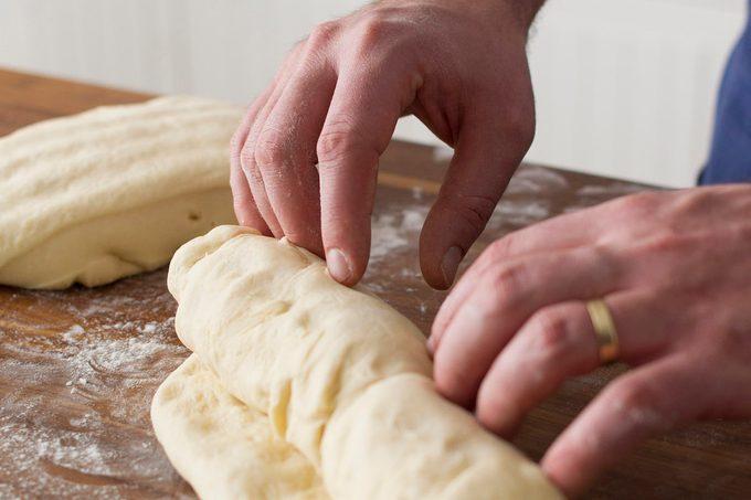 A person kneading sourdough to make a loaf homemade sourdough bread.