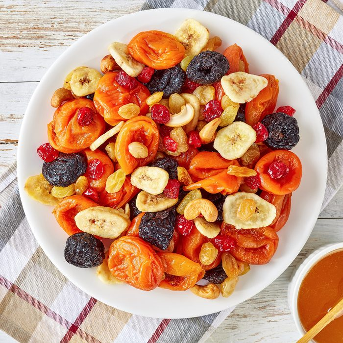 dried Fruits and Nut Mix bowl - banana slices, apricots, raisins, prunes, cherries and cashew on a rustic table with honey in a bowl, horizontal view from above, close-up, flatlay